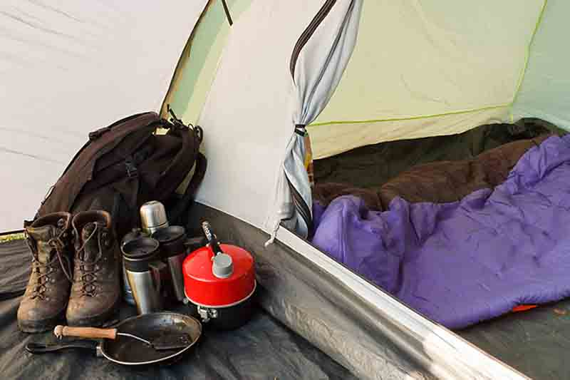Interior view of a tent set up with various equipment and sleeping bag inside inner compartment, and gear in the vestibule, showing a well organized camp.