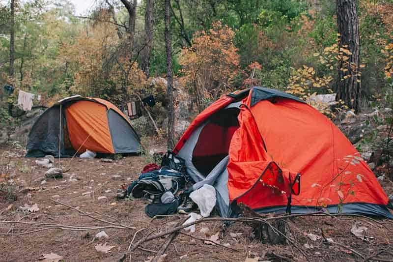 Two rugged tents set up in a clearing in a forest, one red and gray and the other orange and gray. The background is trees with fall colors and in the foreground rocks and vegetation.