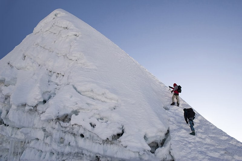 A horizontal image of two climbers on the side of Island Peak mountain.