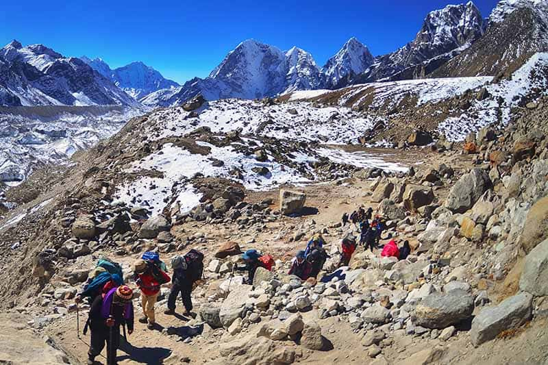 A horizontal image of a group of people backpacking in Nepal pictured on a backdrop of mountains and blue sky.