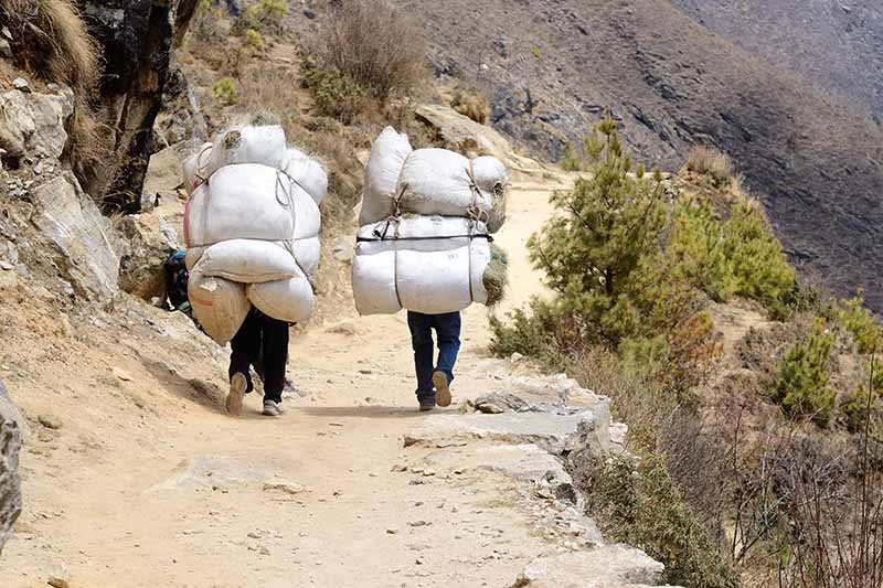 A close up horizontal image of two sherpas trekking in Nepal carrying heavy loads.