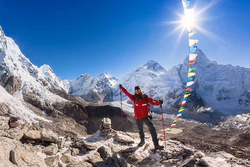 A horizontal image of a man carrying trekking poles pictured with prayer flags and mountains in the background.