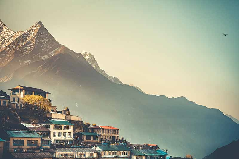 A horizontal image of a view from Namche Bazaar, a village in Nepal with mountains in the background.