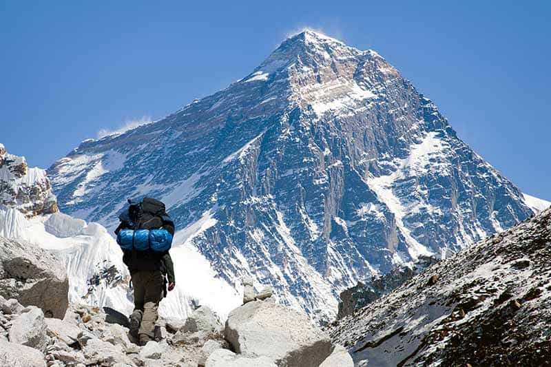A horizontal image of a hiker trekking in the Himalayas with Kala Pattar in the background.