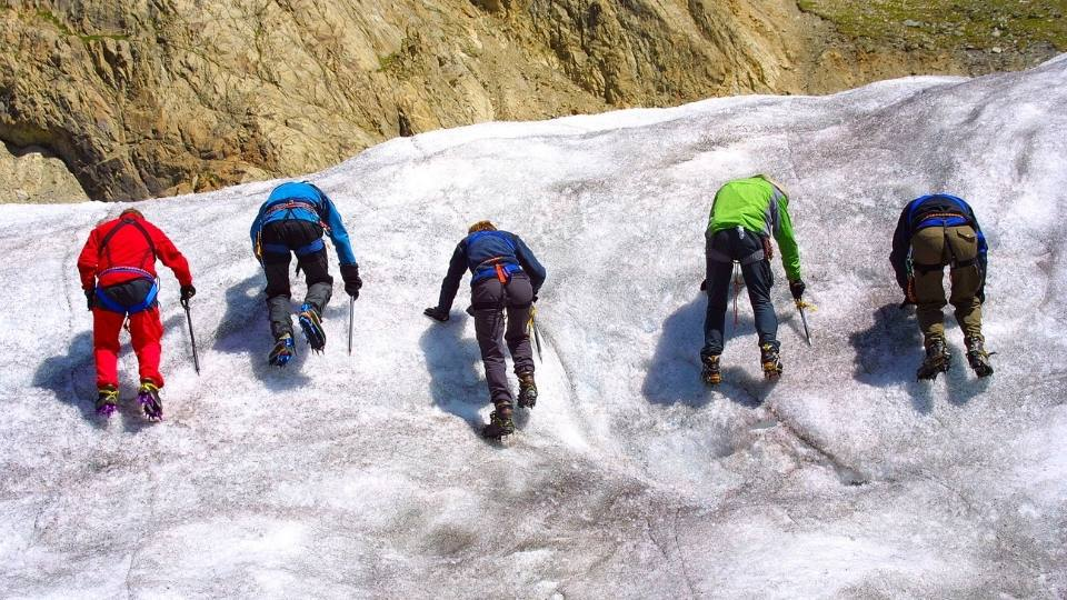 group of  friends using climbing crampons